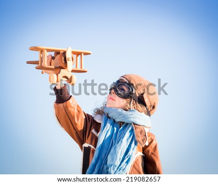 Happy kid playing with toy wooden airplane against winter sky background - stock photo