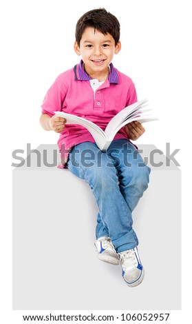 Happy kid reading a book and smiling - isolated over white background - stock photo