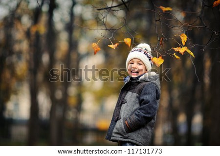 Happy kid standing in autumn park. A boy in a cap and jacket laughs. Cold autumn day. - stock photo
