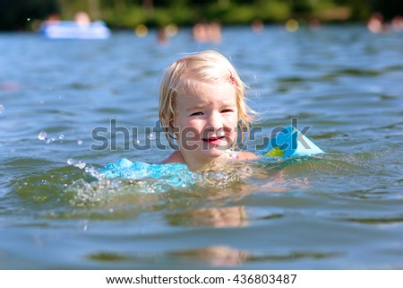 Happy kid swimming in the lake. Healthy smiling toddler girl relaxing in the water wearing inflatable armbands. Active children summer vacation concept. - stock photo