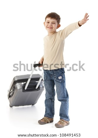 Happy kid traveling with suitcase, waving, smiling. - stock photo