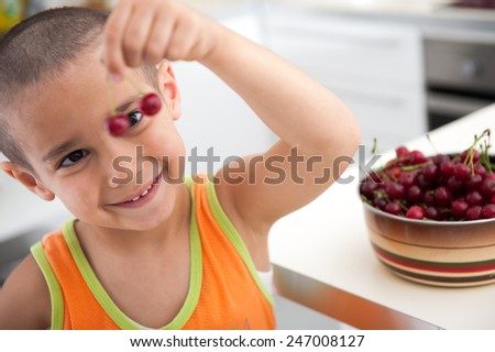Happy kid with healthy food in kitchen - stock photo