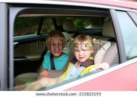 Happy kids, adorable toddler girl with teenager brother sitting together in modern car locked with safety belts enjoying family vacation trip on summer weekend - stock photo