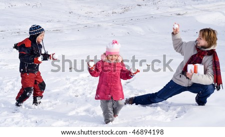 Happy kids and woman playing in the first snow of winter - stock photo