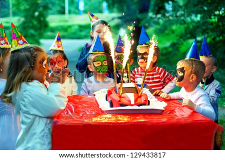 happy kids around birthday cake - stock photo