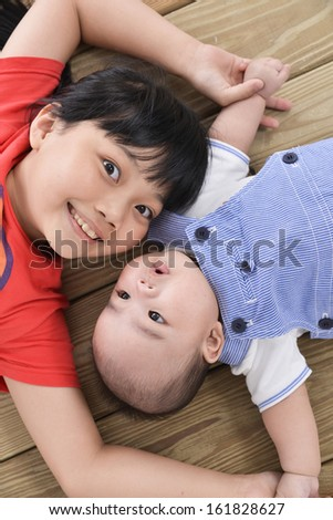 happy kids ,baby on the floor laying on - stock photo