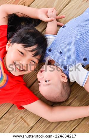happy kids ,baby on the floor laying on wooden floor - stock photo