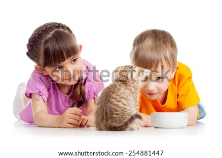 happy kids boy and girl feed cat kitten - stock photo