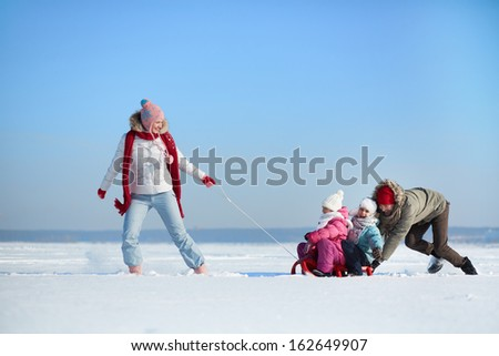 Happy kids enjoying riding on sledge - stock photo