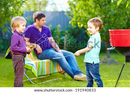 happy kids fighting with kitchen items on picnic - stock photo
