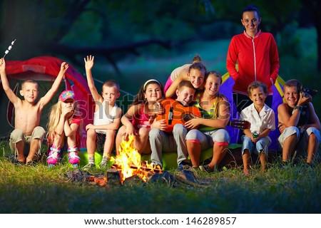 happy kids having fun around camp fire - stock photo
