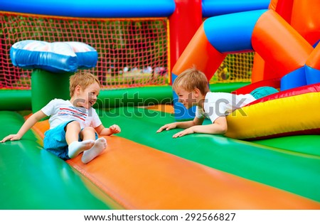 happy kids having fun on inflatable attraction playground - stock photo