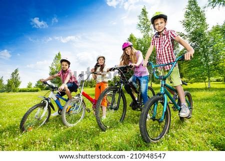 Happy kids in colorful bike helmets holding bikes - stock photo