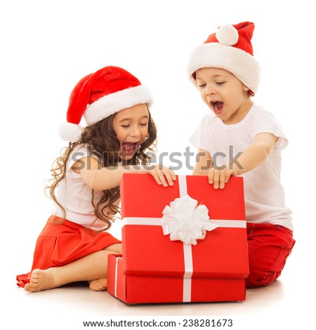 Happy kids in Santa hat opening a gift box. Isolated on white background.  With colorful lights from Christmas tree on background. Holidays, christmas, new year, x-mas concept. - stock photo