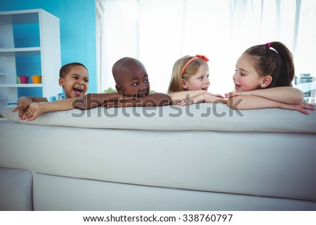 Happy kids looking from the back of the couch - stock photo