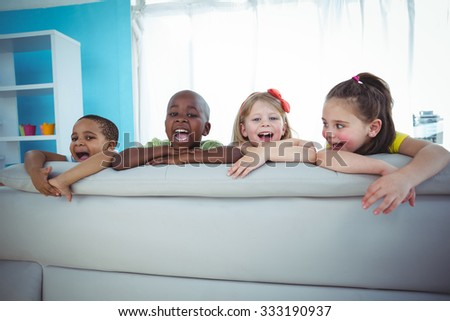 Happy kids looking from the back of the couch and smiling - stock photo