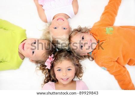 Happy kids lying down on the floor in cross shape - stock photo