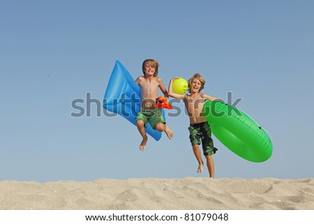 happy kids on summer vacation jumping on the beach - stock photo