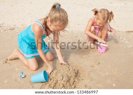 Happy kids playing at the beach - stock photo