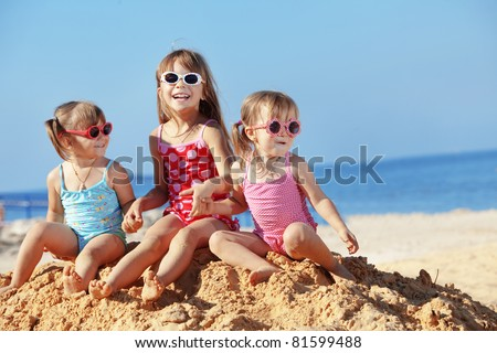 Happy kids playing at the beach in summer - stock photo