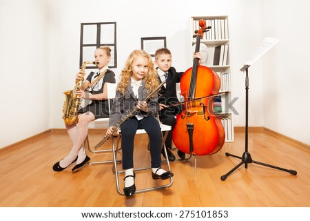 Happy kids playing musical instruments together - stock photo