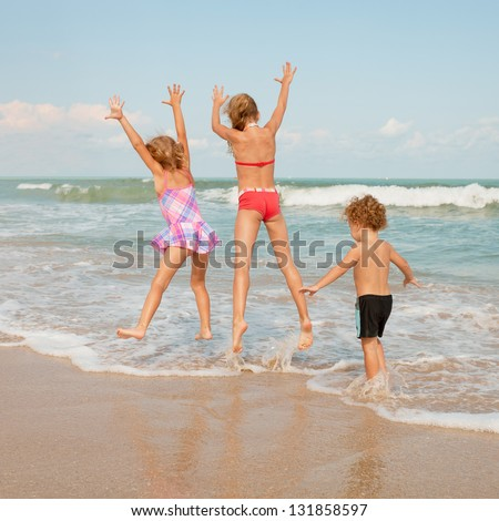 happy kids playing on beach - stock photo