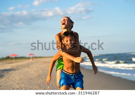 Happy kids playing on the beach on summer holidays. - stock photo