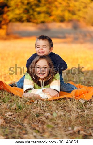 Happy kids playing outdoors in autumn - stock photo