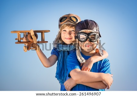 Happy kids playing with vintage wooden airplane. Portrait of children against summer sky background - stock photo