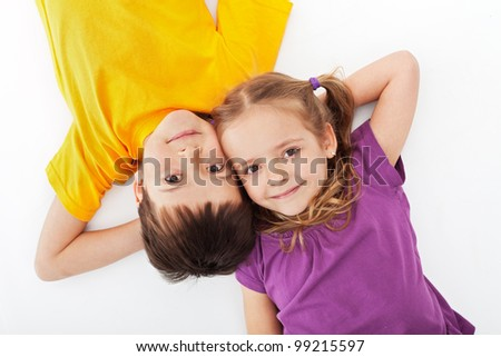 Happy kids relaxing laying on white - top view - stock photo