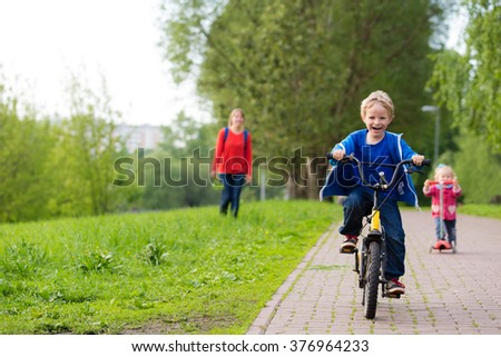 happy kids riding scooter and bike in the park - stock photo