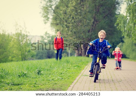happy kids riding scooter and bike in the park, family sport - stock photo