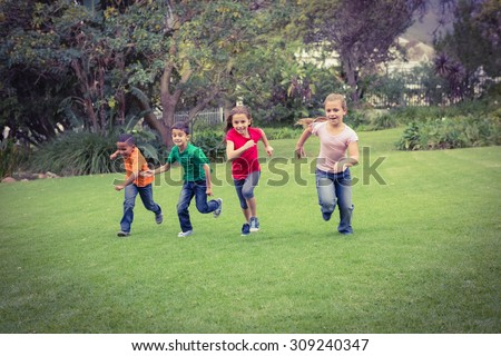 Happy kids running across the grass in a park area - stock photo
