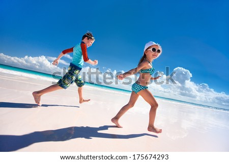Happy kids running and jumping at beach - stock photo