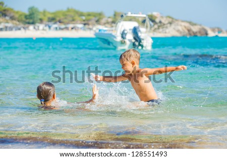 Happy kids. Sister and brother playing and swimming in the transparent sea - stock photo