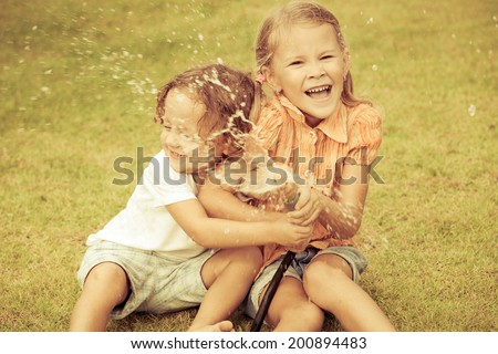 Happy kids sitting on the grass and pouring water from a hose. Concept Brother And Sister Together Forever - stock photo