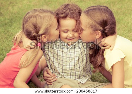 Happy kids sitting on the grass. Concept Brother And Sister Together Forever - stock photo