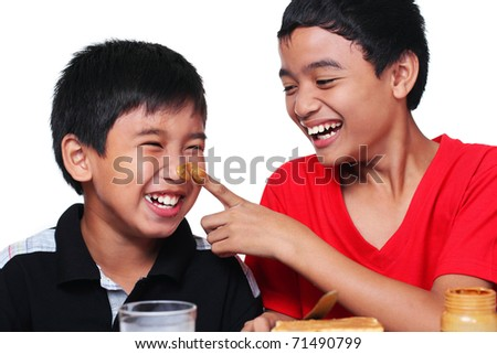 Happy kids smearing faces with peanut butter - stock photo