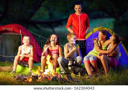 happy kids telling interesting stories around campfire - stock photo