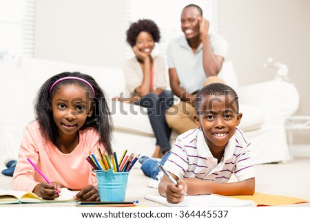 Happy kids using colouring books beside their parents - stock photo