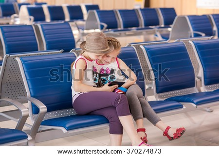 Happy kids waiting for flight inside international airport, playing with tablet PC. Flight delay concept - stock photo