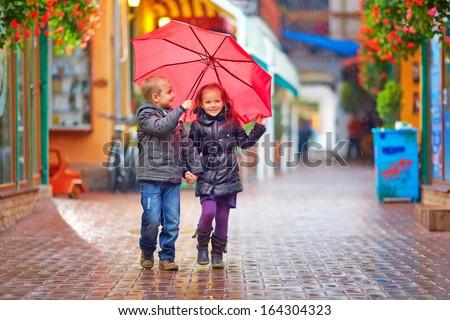 happy kids walking under the rain on colorful street - stock photo