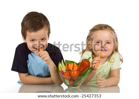 Happy kids with a bowl of vegetables, smiling and eating carrot - isolated - stock photo