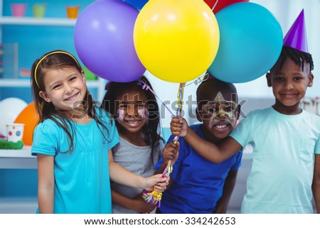Happy kids with balloons at the birthday party - stock photo