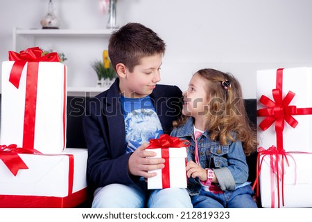 Happy kids with gifts. Red-white concept of gifts - stock photo