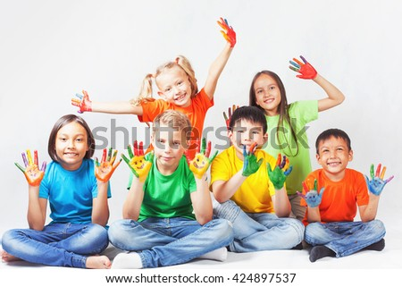 Happy kids with painted hands smiling and posing at white background. - stock photo