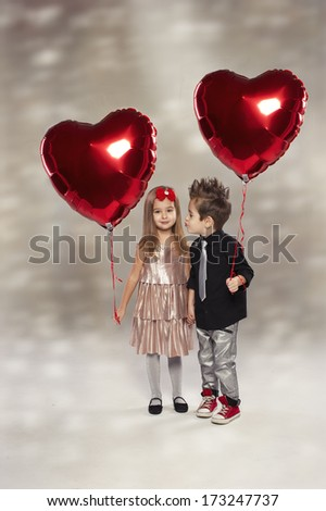 Happy kids with red heart balloon on a light background  - stock photo