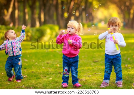 Happy kids with soap bubbles in the park.  fun, children's emotions - stock photo