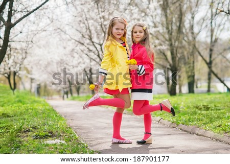 Happy kids with spring flower in blooming garden. Little adorable girls at blossom trees background  - stock photo