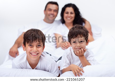 Happy kids with their parents laying in bed on a lazy weekend - stock photo
